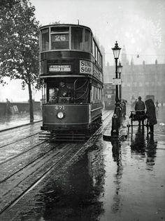 Victoria Embankment on a very wet day in 1931. The No.26 tram is making its way to Blackfriars Bridge and then Southwark Street near London Bridge. It had started its journey at Kew Bridge then along Chiswick High Road, Hammersmith Broadway then over Putney Bridge, Wandsworth High Street, Clapham Junction, Wandsworth Road, Vauxhall Station, Albert Embankment and Westminster Bridge. This route crossed the Thames three times on its way from Kew to London Bridge. Interesting to see the…