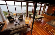 Beautiful hardwood floors in this open-concept living room, dining room and kitchen with views of Gonzales Bay on Vancouver Island.