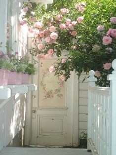 Painted wood panel door used as garden gate...has pink roses painted on it...and pink roses hanging over the fence..love it...
