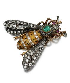 GEM-SET, ENAMEL AND DIAMOND BROOCH, EARLY 20TH CENTURY.  Set with a cabochon emerald and rubies, decorated with yellow and black enamel highlighted with circular- and rose-cut diamonds, French assay and maker's marks.