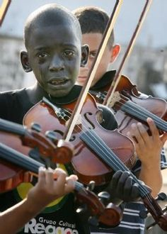 12-year-old, Diego Frazão Torquato playing the violin at his teacher's funeral. The teacher had helped him escape poverty and violence through music.