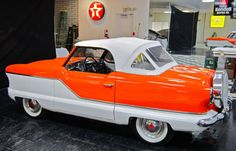 Nash Metropolitan.  I would love to own one someday.  But turquoise instead of orange and hounds tooth interior.  :)