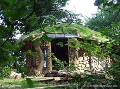 This is Tony Wrench's cordwood roundhouse den in Wales. Like many of Tony's homes it's based on a henge of roundwood timbers with the ends charred and daubed in pitch before being buried in the ground. The roundhouse cost Tony around £100 ($150) to build using timbers from the woodlands that surround his home and some reclaimed windows. More. including video, at www.naturalhomes.org/timeline/roundhouse-den.htm