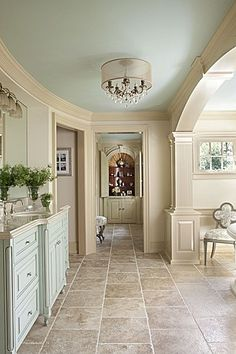 Elegant--------- yet clean and simple, a dream bathroom for the beach----a  cape cod, French, South Hampton home! Beautiful arches and elegant round shade covering the crystal light fixture, with delicious pale green vanity with camel marble counter top tying in nicely with the travertine flooring. All done in the lovely camel colors of the beach! Walls done in a lovely pale yellow/camel color once again tying in nicely with the greens, whites, creams and sand colors of the beach ambiance!