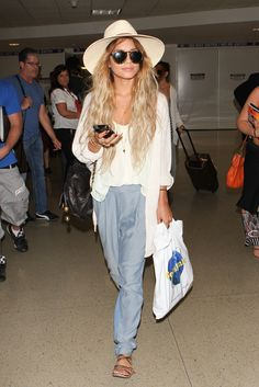 At the airport, Hudgens trys to keep a low profile in large sun hat, cream knits, and slouchy blue pants.   - MarieClaire.com