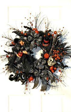 Extra Large Witch Wreath in Black and Orange. There is a stunning Large Resin Witch holding a jack o lantern - sitting next to a Spooky