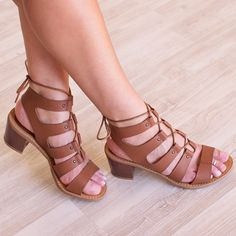 So, why don't you own these yet? Our Yvette Lace Up Low Heel Sandal in tan features a supple, faux leather material in a caged, open-strap style with adjustable brown laces woven through that tie arou