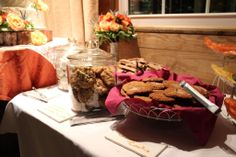 wire basket lined with linen napkin for cookies along with clear glass containers. Khimaira Farm