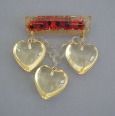 Shultz Lucite reverse carved orange daisies brooch with dangling hearts
