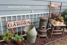 """The new  old"""" pails join a newly created vignette with terra cotta pots, and the bean pots that were too shaded on the covered patio and not blooming well.  An old futon metal back is repurposed as a fence."""