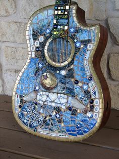 Rhythm & Blues Mosaic Guitar ~ Blue stained glass from Vancouver, WA, from a small stained glass factory that has closed its doors. Vintage jewelry, wings from a broken figurine, broken plates, mirror, smalti, 23K gold plate rims, dichroic glass, beads, and dichroic stringers from Helios Glass.