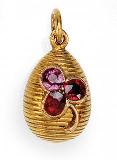 A FABERGÉ JEWELLED GOLD EGG PENDANT, WORKMASTER AUGUST HOLLMING, ST PETERSBURG, 1908-1917 - the ribbed body set with a trefoil of one pink and two red faceted stones, 56 standard. via Sotheby's.