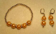 Orange pearls, rhinestone spacers and gold beaded stretch bracelet and matching earrings.