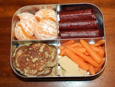 Clementine halves, beef sticks, carrots sticks and hummus and pancakes–zucchini latkes in the LunchBots Quad