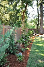 Like this simple landscape lining the fence. Could add pretty annuals in there in the summer!