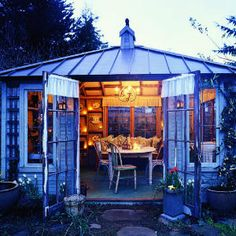 """Summer living room In a Shed built in a backyard.  Recycled wood makes this new """"family shed"""" used for desk work and summer dining look old. Details like the skirting for the vintage bathroom sink add to the illusion of a building that's been on the site for a long time."""