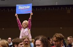 """Five-year-old Courtney Skinner holds up a """"Bernie Sanders for President"""" sign at the Juneau Democratic Caucus."""