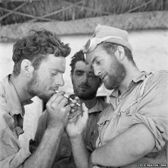 British soldiers share a light, c. 1943