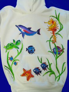 Pullover hooded sweatshirt hand painted with sealife, including a seahorse, turtle, dolphin, and colorful fish.