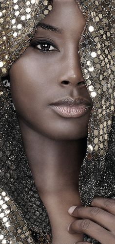 Super gorgeous look for brown skin, light browny-orange lips, black liquid liner highlights dark brown eyes, gold material/ scarf draped around face.