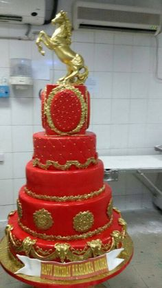 Gorgeous red cake with gold accents, and a golden horse as topper
