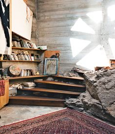Countercultural architect Paolo Soleri looked beyond the bounds of four walls and a roof to orchestrate his vision for comprehensive ecological design.  A handful of operations staff live in on-site apartments. Rather than dig out a boulder that's part of the mesa Arcosanti rests upon, builders incorporated it into the room. Woodworker Tim Daulton constructed the staircase. Photo by: Peter Bohler