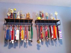 Save your walls...hang ribbons and medals from wine glass holders!
