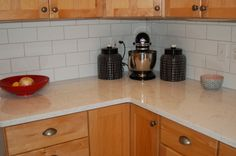 white quartz counters, white subway tile, gray grout, light brown cabinets