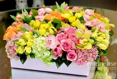"""Spring Mix 50  Description:A mesmerizing and vibrant mix of Dutch Tulips, South American Roses, Hydrangeas and Orchids all arranged in a pink, 16"""" x 16"""" linen covered box. This arrangement is approx. 9"""" tall."""