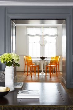 An orange hue adds a pop of color to this dining area. Design by Spencer & Wedekind.