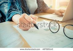 close up hand of business women holding pen pointing on paper graph chart and using laptop on wooden desk indoor office. vintage filter effect.
