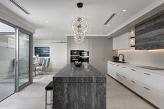 Fabulous modern kitchen with white cabinetry and grey breakfast island by leading Perth luxury home builder.