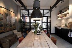 cuisine industrielle aménagée avec un mobilier en bois, noir et blanc et décorée d'un mur de béton exposé et d'une crédence en carrelage métro blanc