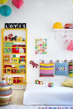 Colorful striped rug, bright-colored pillows, hanging paper balls, flash cards display which I have; yellow, green, red, pink all work together