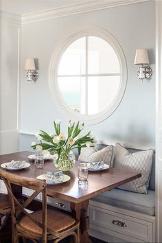 Chic breakfast room features a round window lit by Jonathan Sconces placed over a built in banquette with drawers lined with blue cushions and blue striped pillows facing a trestle dining table lined with French cafe chairs.