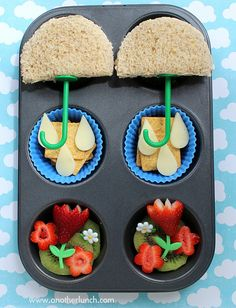 April Showers Bring May Flowers theme lunch - 2 umbrella sandwiches, havarti cheese raindrops on crackers, strawberry flowers on a kiwi backdrop, and bento picks make the tulip stems and pretty daisies.
