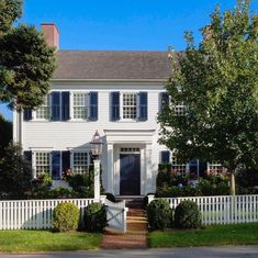 White clapboards crisp navy blue shutters on twelve over twelve windows a perfect picket fence.the definition of New England charm and Colonial House Exteriors, Colonial Exterior, House Paint Exterior, Exterior Paint Colors, Exterior House Colors, Paint Colors For Home, Blue Shutters, World Of Interiors, Interior Barn Doors
