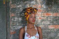 Nyarai wears our headwrap ELLA teamed with a loose floral cotton top and yellow shell earrings.