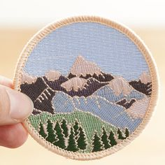 The perfect patch for an explorer, pop it on your rucksack and get hiking! This patch makes a great gift for someone that loves the outdoors. Lose yourself in this wilderness patch. A beautiful mountain patch. An embroidered iron-on patch, based on a watercolour illustration of