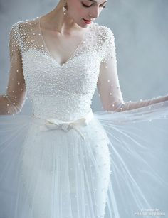 a gorgeous pearl wedding dress with an illusion neckline, illusion pearled sleeves and an overskirt to sparkle