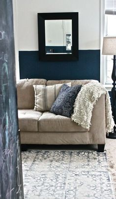 navy blue and white wall, with a neutral couch, and blue, white and black accents