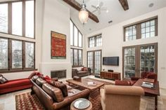 Two storied room with beamed ceilings and fireplace , floor to ceiling architectural windows flanked by two patios brings the outside in
