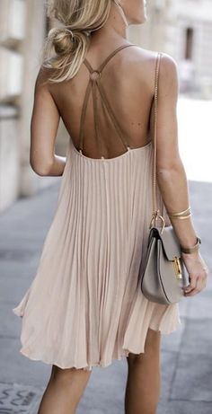 Tan pleated dress with open detailed back styled with leather crossbody and simple bangles.