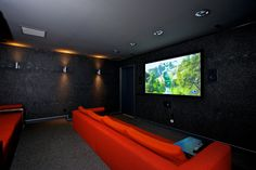Here's another angle of this incredible almost movie like home movie theater. This perspective shows the wall lighting fixtures. a different angle of the red velvet silk sofas, projection screen, and, dark purple walls.