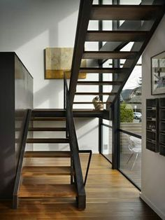 The little house has a grand entrance with the open custom steel staircase just off the front door. The staircase and perforated-steel fireplace, left, shield the living spaces from street view. Industrial baking pans, right, hold phones, keys, glasses and other whatnots. The encaustic is by Caite Dheere of Victoria, B.C.