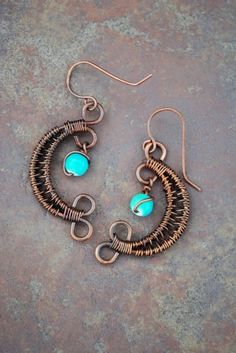 These Kokopelli-like earrings are hand made with wrapped copper wire.  A roughly 5.5mm aqua-colored ceramic bead dangles from the top, and it all hangs from handmade ear wires.  These are right at 2&#