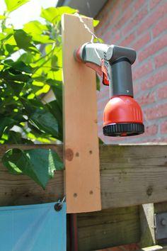 Plankje met gat aan de schutting. Gardena broeskop. Aansluiten op mengkraan in de keuken.
