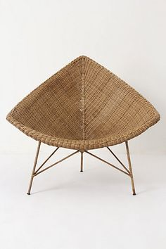 """Naida Chair:  """"A juxtaposition of modern and natural, this sleek silhouette of hand-woven wicker stands atop spindly steel legs."""""""