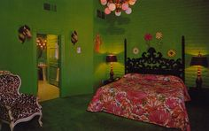 An eclectic bedroom with vintage touches, featuring bright green walls, plush green carpeting, and a pink floral bedspread.