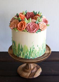 Gâteau de mariage orné de roses, dans les tons vert et orangé